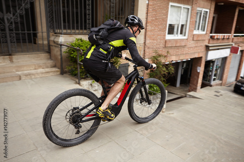 Poster Side shot of male cyclist wearing cycling clothing and protective gear speeding on streets riding his pedal-assist electric bike, about to jump down concrete stairs