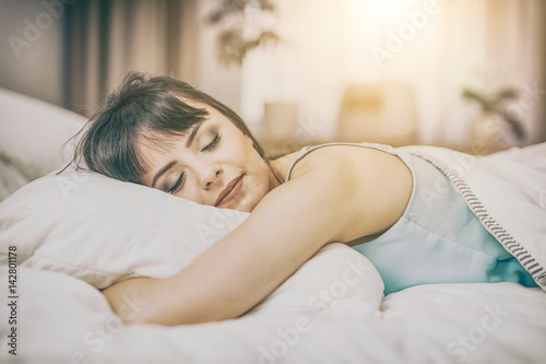 Beautiful young woman sleeping on a bed in the bedroom.