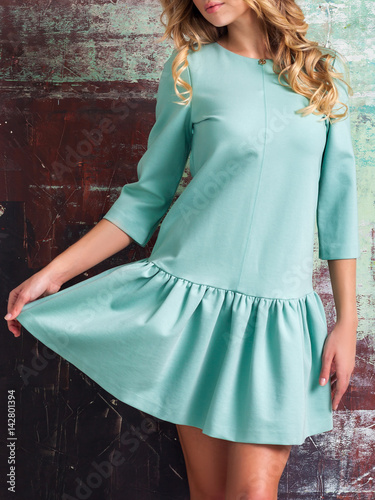 Plakat Young fashionable blond woman in blue short dress