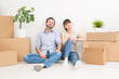A young couple sitting on the floor and looking up. Dream and enjoy a new home.