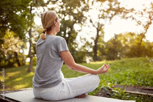 Female in lotus pose in park Poster