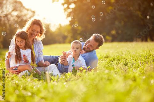 Children in nature make soap bubbles