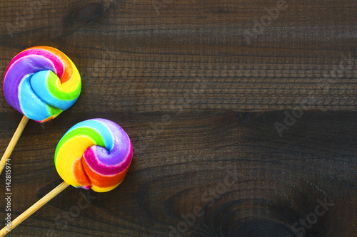 two rainbow colored lollipops on blue wooden background Poster