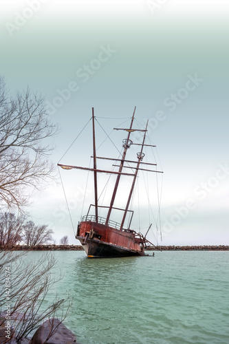 Rusty shipwreck with tall masts in a cover near shore, dark stormy sky above