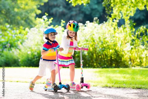 Fotografiet Kids riding scooter in summer park.