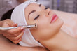 Leinwandbild Motiv The doctor-cosmetologist makes the procedure Microdermabrasion of the facial skin of a beautiful, young woman in a beauty salon.Cosmetology and professional skin care.