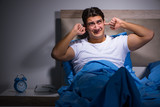 Fototapety Young man struggling from noise in bed