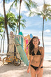 Woman surfer at beach surf school surfboard rental. Asian bikini girl walking next to rack of many boards to rent for lessons in Honolulu City, Oahu, Hawaii, USA.