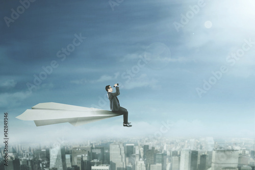 Plakat Entrepreneur with binoculars on paper plane