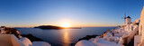 Traditional apartments and windmills in Oia village on a sunset, panoramic image