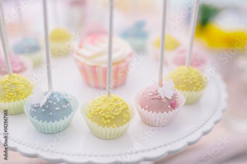 Poster Rosa Cupcake umrahmt von Cakepops süßer bunter Teller