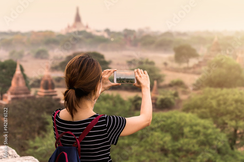 Female traveler photographing ancient pagoda at Bagan Poster