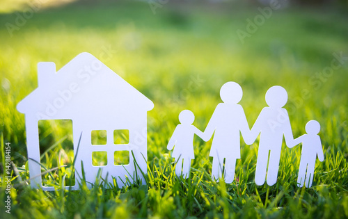 Paper cut family with house in green grass background