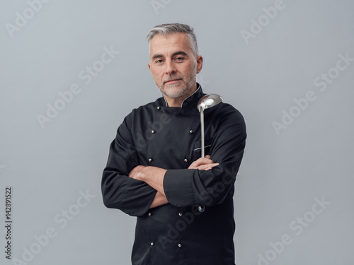 Chef posing with a spoon ladle Poster