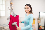 Happy young asian woman steaming clothes in room