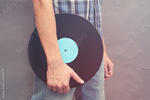 Man holds vinyl record in his hand Poster