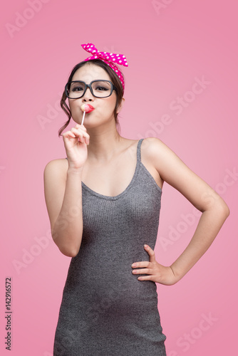 Portrait of beautiful asian woman eating heart shape lollipop, dressed and makeup in pin-up style on pink background Poster