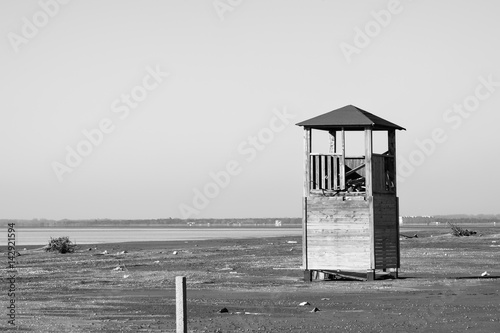 Old tower for lifeguards on the deserted beach in black and white - 142921594
