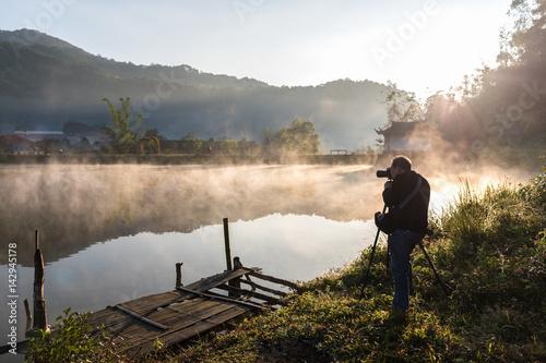 Photographer taking photo of amazing landscape sunrise.
