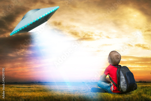 The little boy looks up at an unidentified flying object which appeared in the sky Poster