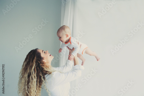 happy family at home. Mother holding baby son in bedroom in cozy weekend morning