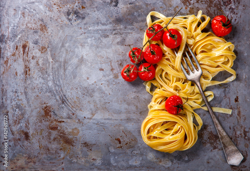 Pasta Tagliatelle is traditional, on a metal Baking sheet with roasted Vegetables,cherry Tomatoes.Copy space for Text. selective focus.