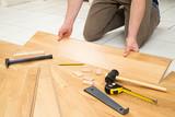 young man at parquet flooring work / junger mann beim verlegen von Parkett - 142971591