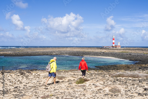 Deurstickers Canarische Eilanden Hikers on their track to the lighthouse Faro del Tostón at the north cape of Fuerteventura Canary Islands near the village El Cotillo.