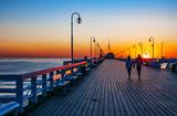 Wschód słońca na drewnianym molo w Sopocie, Polska i nierozpoznawalna para chodząca