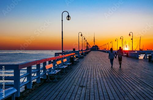Sunrise at the wooden pier (molo) in Sopot, Poland and an unrecognizable walking couple