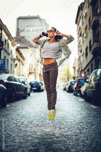 Cheerful woman listening to music via headphones on the street  - 143001304