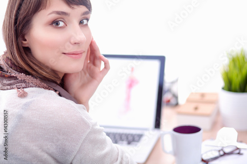 Portrait of attractive female fashion designer sitting at office desk Poster
