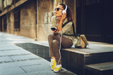 Fototapeta Young woman listening to music via headphones on the street
