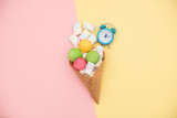 photo of tasty colorful marshmallows in waffle cone and alarm clock on the wonderful colorful background in pop art style