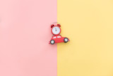 photo of car shaped toy and alarm clock on the wonderful background in pop art style