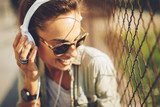Happy young woman listening to music via headphones on the street on a sunny day - 143025371