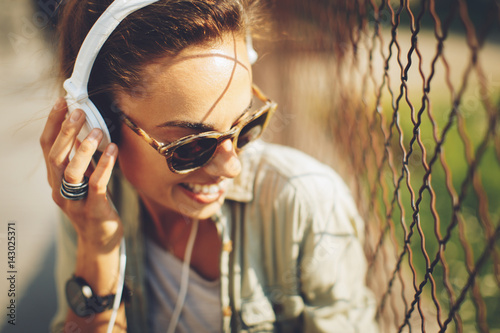 Sticker Happy young woman listening to music via headphones on the street on a sunny day