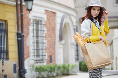 Woman with bread in a bag on the street of Paris