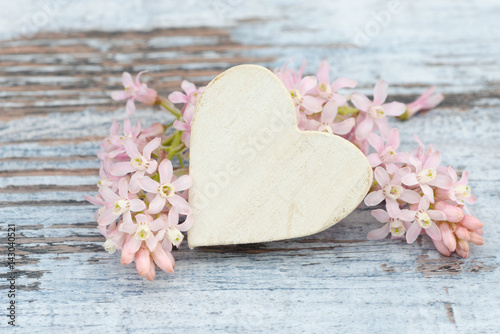 heart and flower lying on wood