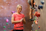 young woman exercising at indoor climbing gym wall - 143056570