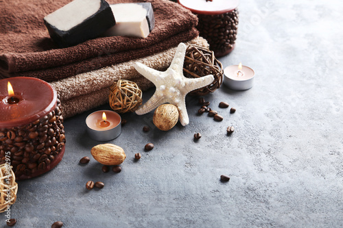 Poster Towels with candles and soap on grey wooden table