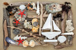 Beach Art Abstract. with driftwood, seashells, rocks, seaweed and decorative sailing boat on sand background.