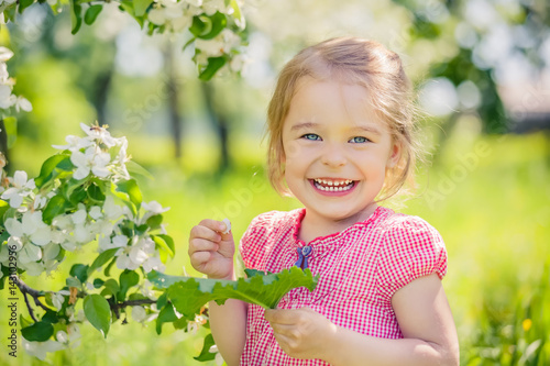 Happy little girl playing in spring apple tree garden Poster