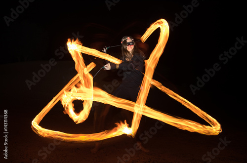 Dancer with flaming fire pois after dark.