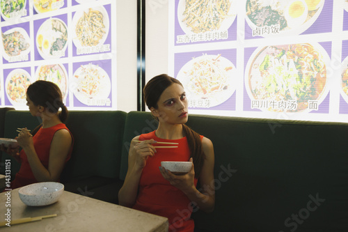 Young woman eating in eatery