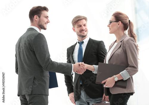 Handshake between business people in a modern office Poster