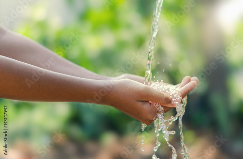 Water pouring in kid two hand on nature background - 143147937