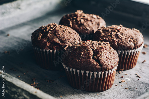 Chocolate muffins on gray wooden tray