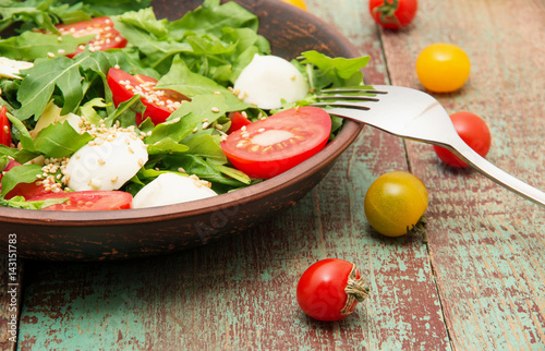 Green salad made with arugula, tomatoes, cheese mozzarella balls and sesame on plate