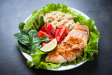 Fresh salad from quinoa, chicken breast, spinach, lettuce and tomatoes. Organic food. Healthy meal portion plate.